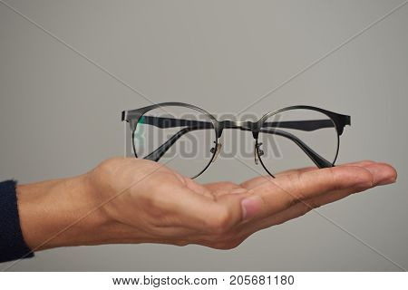 Glasses on human lay hand close up isolated on gray background