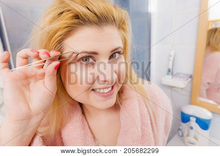 Woman Tweezing Eyebrows Depilating With Tweezers