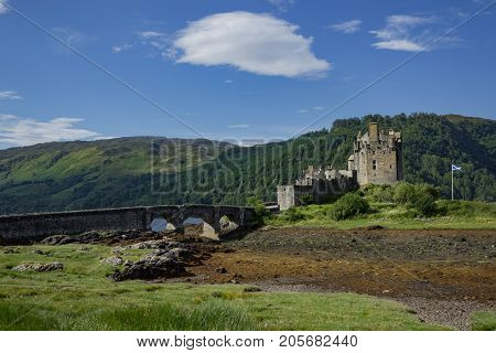 Full footbridge and Scottish Flag waving during low tide at Eilean Donan Castle on a summer's day.