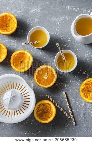 Cut oranges fresh orange juice manual citrus juicer on a grey table top view. Healthy food concept