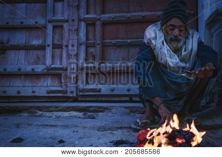 Pushkar India : 17th February 2015 - A shot of a homeless person keeping warm by the fire in the street of Pushkar India in a cold morning.