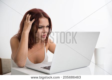 Portrait of displeased young Caucasian businesswoman sitting at laptop and having problem of computer error or bug on her laptop