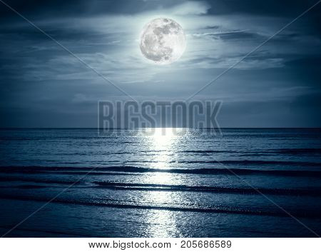 Colorful Sky With Dark Cloud And Bright Full Moon Over Seascape.