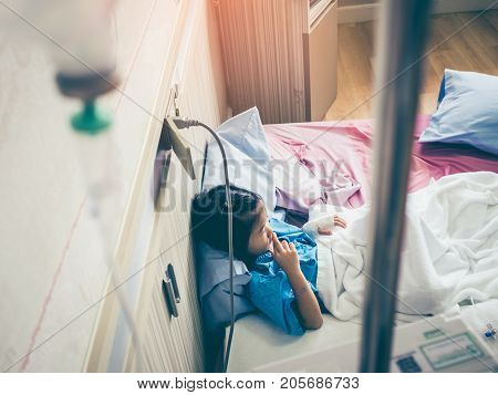 Illness Asian Girl Sitting On Sickbed In Hospital With Intravenous Iv Drip.