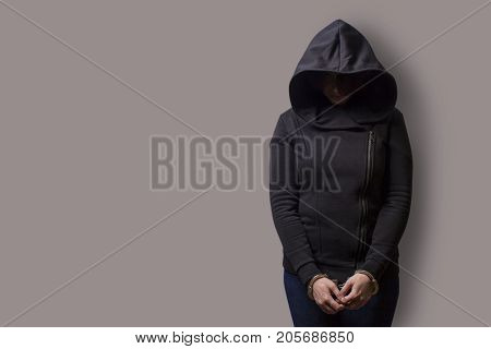 front view of a girl in a black hood with handcuffed hands isolated on a gray