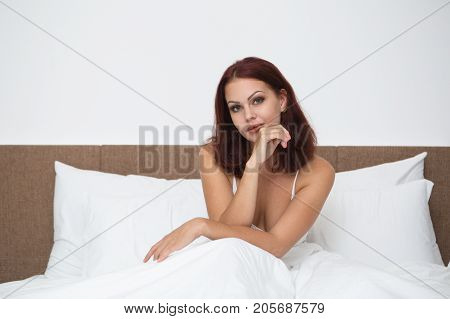 Portrait of young Caucasian woman sitting under duvet in bed, looking at camera and smiling in morning
