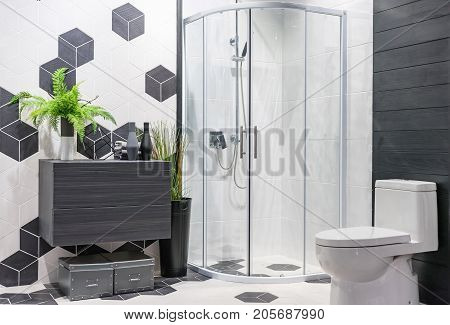 Modern spacious bathroom with bright tiles with glass shower toilet and sink. Side view