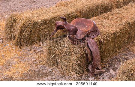 Photo of leather cowboy saddle hanging on hay.
