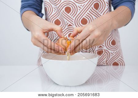 Close-up of woman cooking favorite dessert. Unrecognizable chef pressing thumbs against indentation on egg and pulling egg apart to release shell into bowl. Cooking workshop concept