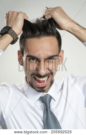 Young Man In Business Attire Pulling Hair In Frustration