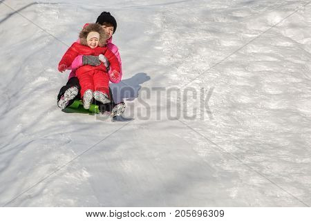 Happy mother and her daughter enjoying a sledge ride down the hills winter games and fun. Family holiday and togetherness.