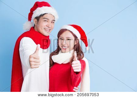 couple smile and thumb up with merry christmas on the blue background