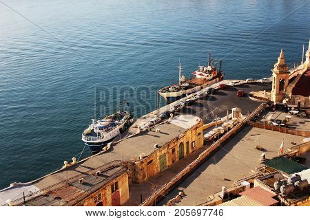 Panoramic skyline view of ancient defences of Valletta and the Grand Harbor with ships .
