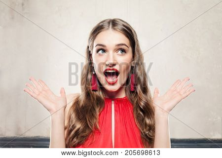 Surprised Fashion Model Girl with Open Mouth. Perfect Woman with Makeup and Red Earrings on Background