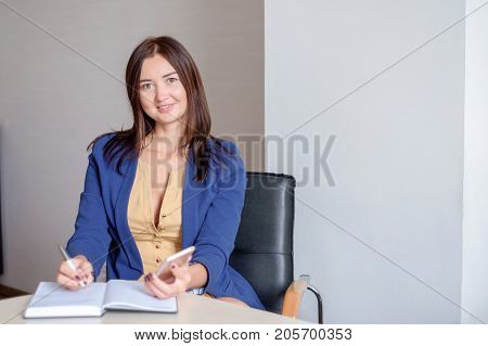 busy secretary is answering call and writing memo at the same time.