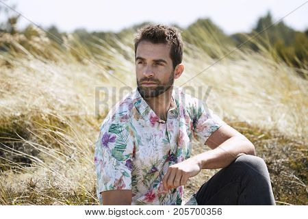 Handsome guy with stubble and floral shirt looking away