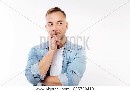 Pensive mood. The portrait of a handsome bristled man in a denim shirt holding his hand near the face, resting a chin on it and thinking about something while isolated on white background