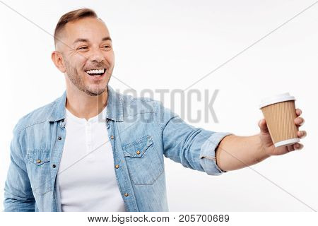 Tempting offer. Happy pleasant young man stretching a hand with a paper cup of coffee as offering someone to taste it while smiling broadly