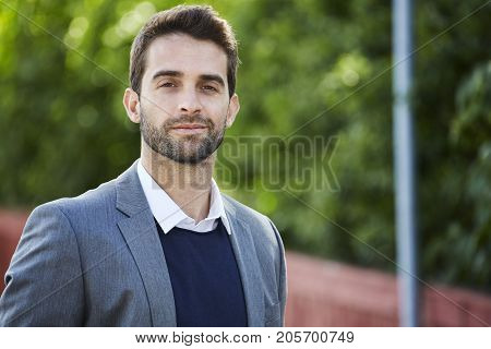 Handsome stubble man in grey suit jacket smiling