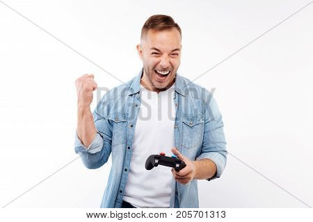 Happy victory. Overjoyed young man holding a game controller and raising hand in a celebratory gesture as if after the victory in game while isolated on white background