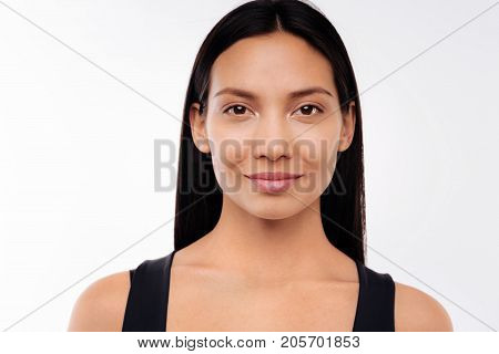 Natural beauty. The portrait of a pretty black-haired woman in a black tank top posing on a white background and smiling at the camera