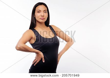 Stunning appeal. Gorgeous black-haired young woman in a black tank top posing on a white background, holding her hands on waist while standing half-turned