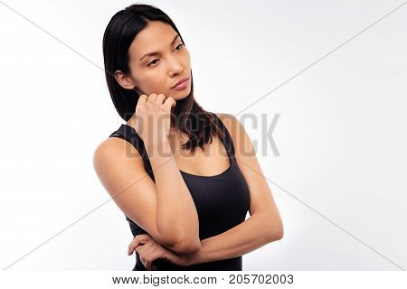 Wistful mood. Beautiful black-haired young woman in a black tank top resting her face on hand while being deep in thought