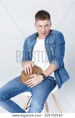 handsome shy man in denim and hat  sits on chair on white background