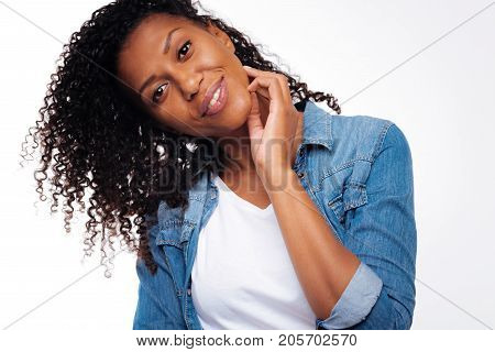 Sensual pose. The portrait of a beautiful curly black-haired woman tilting her head to the side and touching her neck with a hand