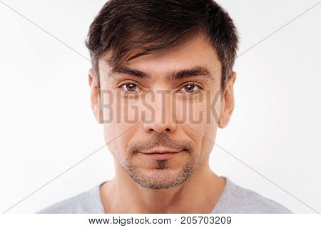 Epitome of masculinity. The close up of a handsome black-haired bristled man looking at the camera while posing on a white background