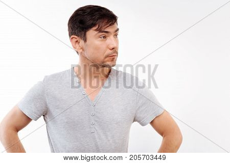 Like a boss. Charming dark-haired man in a grey t-shirt posing on a white background and holding his hands on waist while looking into the distance