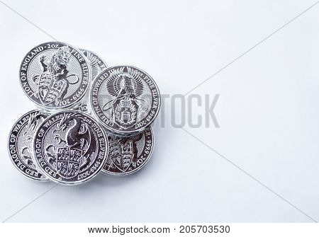 On a gray background are silver coins of an investment silver from a British mints. Dragon of Wales Lion of England and Griffin of Edward III. Empty space for text input.