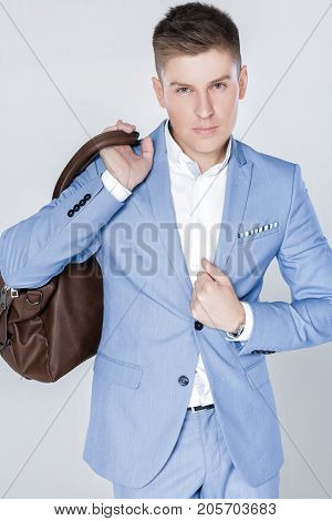 Handsome fashion young man in blue suit carrying leather bag on shoulder and looking at camera against grey background