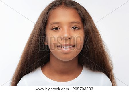 Innocent child. The portrait of a charming pre-teen girl with a swarthy complexion and auburn hair posing on a white background