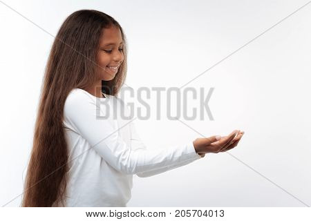 Precious little things. Charming pre-teen girl with a swarthy complexion and a long auburn hair stretching out her hands and cupping them as if holding something small and precious