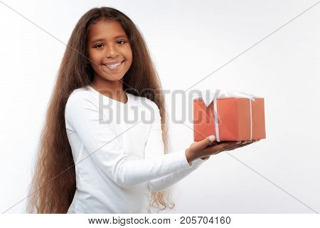 Happy birthday. Beautiful pre-teen girl with a swarthy complexion and long auburn hair posing on a white background while holding a box with a gift