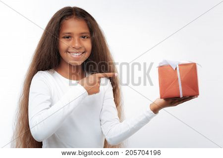 Gift for you. Pleasant cheerful girl with a long auburn hair posing on a white background and pointing at the gift box with her index finger
