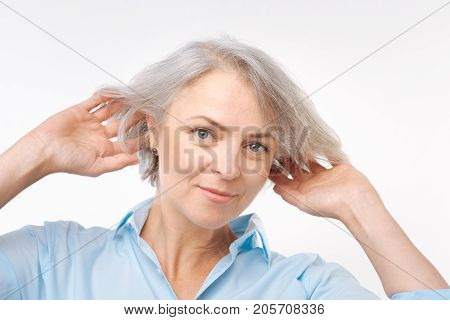 Natural attractiveness. Beautiful grey-haired grey-eyed woman in a baby blue shirt posing on a white background while lifting up her hair with both hands