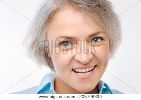 Toothy smile. The close up of a charming grey-haired woman posing on a white background and grinning at the camera poster