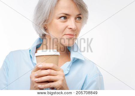 Caffeine dependent. The close up of a pretty grey-haired middle-aged woman posing on a white background while cupping a paper cup of coffee in her hands