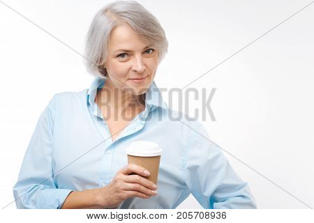 Adore this drink. Beautiful senior grey-haired woman in a baby blue shirt posing on a white background with a paper cup of coffee in her hand