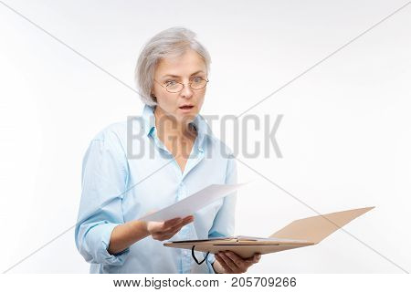 Shocking results. Pretty grey-haired woman holding a paper folder full of research results, looking through them and looking dumbfounded