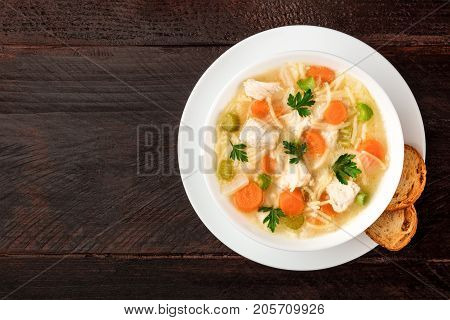 An overhead photo of a plate of chicken, vegetables, and noodles soup, shot from above on a dark rustic texture with slices of bread, and a place for text