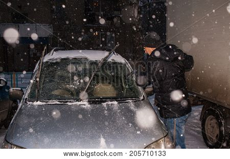 A male in black jacket is cleaning windshield of car from adhering snow during snowfall in winter evening.