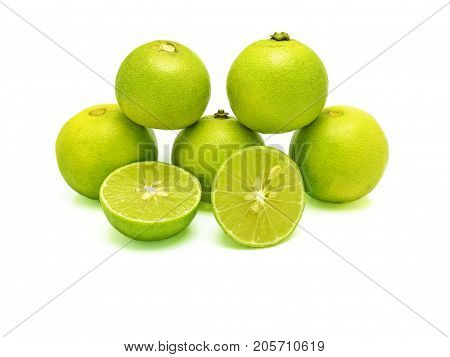 Five green limes (in pyramid stacking) and two splitted halves on white background. A kind of fruit used as an ingredient for cooking, especially in sour food. Scientific name - Citrus x aurantiifolia