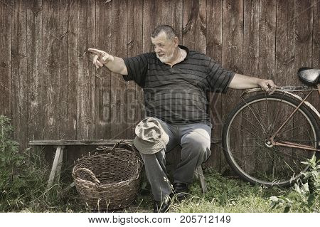 Toned image of smiling Ukrainian senior peasant sitting on a bench at summer day and pointing to somewhere