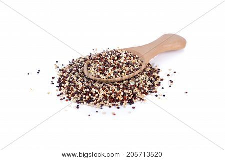 dry tricolor quinoa in wooden spoon and on white background