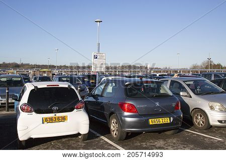 Swansea, UK: December 28, 2016: A parking notice stating the terms and conditions of use and fine if overstaying the four hour limit amongst the cars parked in the free car park at a Tesco Extra.