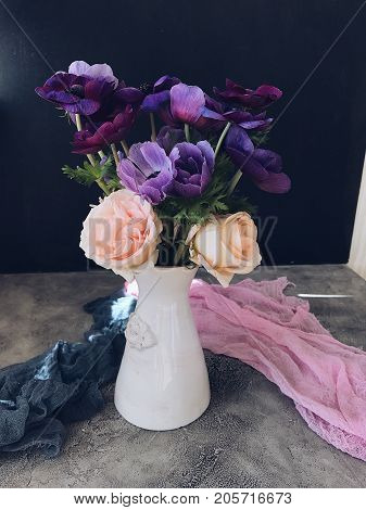 vase with flowers on a dark table