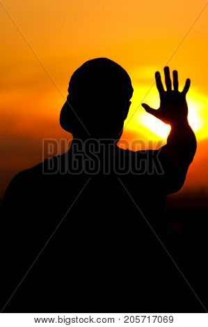 Silhouette of relaxed man enjoying sunset time. Relaxation and leisure concept.